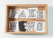 NOTÍCIA da FALSIFICAÇÃO do texto feita das letras na caixa de madeira no fundo branco fotos de stock