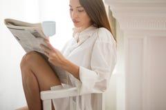 Notícia da leitura da mulher durante o café da manhã Imagens de Stock Royalty Free