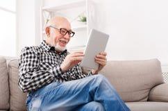Notícia da leitura do homem superior na tabuleta digital imagens de stock