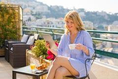 Notícia da manhã da leitura da mulher na tabuleta ao comer o café da manhã no balcão Imagens de Stock