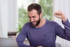 Notícia de leitura do homem considerável feliz boa no portátil Imagem de Stock