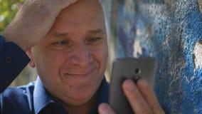 Notícia de sorriso surpreendida da leitura feliz da pessoa boa no telefone celular foto de stock