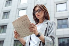 Notícia diária Jovem senhora nos monóculos que estão no close-up interessado do jornal da leitura da rua da cidade imagem de stock