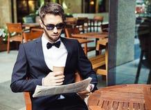 Notícia e café Homem de negócios novo que lê o papel de manhã, café bebendo em um prédio de escritórios do café Fim acima Fotos de Stock Royalty Free