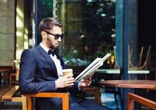 Notícia e café Homem de negócios novo que lê o papel de manhã, café bebendo em um prédio de escritórios do café Ruptura de café Fotografia de Stock Royalty Free