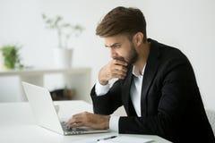 Notícia em linha de leitura de pensamento focalizada do homem de negócios sério usando l foto de stock