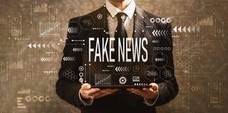 Notícia falsificada com o homem de negócios que guarda um tablet pc imagem de stock royalty free