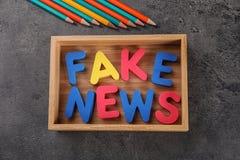 A NOTÍCIA FALSIFICADA da frase fez com letras da cor na caixa de madeira no fundo cinzento fotografia de stock
