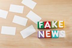 A NOTÍCIA FALSIFICADA da frase fez dos cubos com letras no fundo de madeira imagem de stock