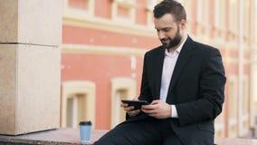 Notícia farpada nova da leitura do homem de negócios no tablet pc durante a ruptura na rua da cidade filme