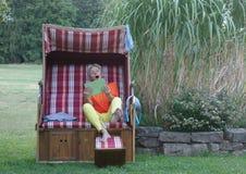 A notícia surpreendente alcança a jovem mulher na cadeira de praia de vime telhada com sua tabuleta imagens de stock royalty free
