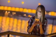 Notícia triste A jovem mulher virada com telefone celular lê a mensagem Foto de Stock Royalty Free