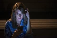 Notícia triste A jovem mulher virada com telefone celular lê a mensagem Imagem de Stock