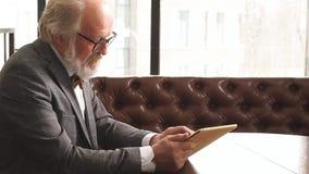 Notícias de negócios de observação à moda do homem mais idoso na tabuleta video estoque