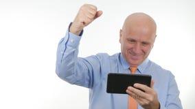 Notícias financeiras de Use Tablet Read do homem de negócios feliz as boas fazem Victory Hand Gestures fotografia de stock royalty free