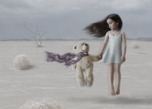 Not Alone. Little girl holding a bear paw with scarf fluttering in the wind against the backdrop of cloudy weathe Royalty Free Stock Image