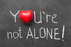 Not alone. You're not alone exclamation handwritten on blackboard with heart symbol instead of O Stock Image