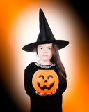 Not Amused. A young witch holds a jack o'lantern royalty free stock photography