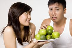 Not Apples Again. A healthy looking asian woman passes a plate of green fruits to her male friend who looks disappointed Stock Photos