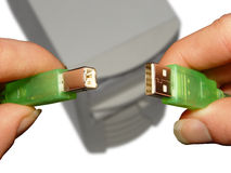 Not compatible (clipping path). Male hands holding two different USB plugs over a blured computer case. clipping path for hands and plugs (in high resolution Stock Image