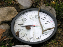 Not enough time. An abandoned, broken clock in amongst some rocks Royalty Free Stock Photos