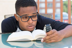 Not enough time. Closeup portrait, nerdy young man in big black glasses holding watch, falling very tired of reading, isolated outdoors outside background. The royalty free stock image