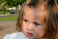 Not So Fast... Closeup portrait of a little girl outside on a playground, with a questioning expression stock photo