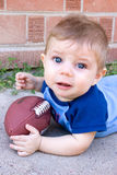 Not Football. A baby boy unhappy about playing  with his football Royalty Free Stock Images