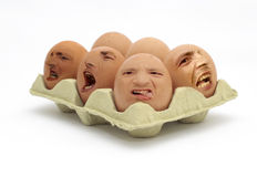 Not Free Range Eggs!. A box of annoyed, angry and deformed eggs Royalty Free Stock Photo