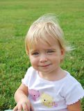 Not going to smile. Toddler girl sitting on grass Stock Image