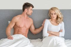 Not in Good Terms Young Couple on Bed. With White Cover with Gray Wall Background Royalty Free Stock Images