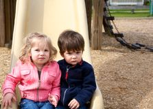 Not so happy. Boy and girl sitting together at the end of a slide in a park Royalty Free Stock Image