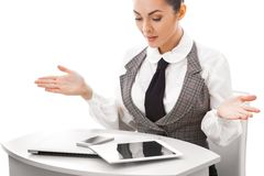 Not Happy Computer User, Feeling Frustrated. Young business woman sitting at table with a laptop and tablet pc, arms raised in quastion Stock Photography