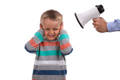 Not listening. Father or teacher telling off son or pupil by shouting through a megaphone whilst his hands covering ears not listening Stock Photo
