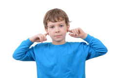 Not Listening. Young boy with finger in ears isolated white background Stock Photo