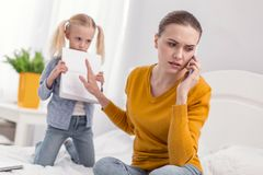 Angry sad mom having no time for daughter. Not now.Pretty charming displeased mom communicating on phone while frowning and turning away from daughter Royalty Free Stock Photo