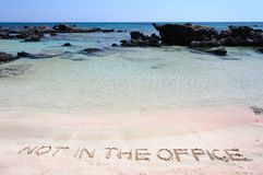 NOT IN THE OFFICE written on sand on a beautiful beach, blue waves in background Royalty Free Stock Photo