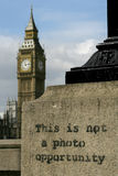 Not a photo opportunity. Graffiti on a lamp-post across the Thames river from Big Ben in London. Big Ben is slighty out of focus in the distance while the royalty free stock image