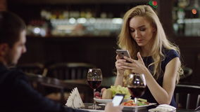 Not romantic pair using phones in restaurant. Lovers with mobiles. pair using smartphone during dating in restaurant stock video
