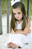 Not Smiling. Little girl frowning sitting on the beach by a wooden fence dressed in a white dress with a big bow in her brunette hair Royalty Free Stock Images