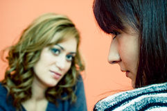 Not Talking. Two women, blond with head tilted and eyes focused toward the brunette, who is being evasive. Focus is on the brunette royalty free stock image