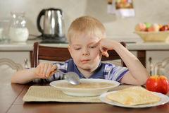 Not a tasty dinner. The boy behind a table during a dinner does not wish to eat soup stock photos