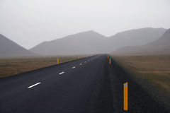 The Not Too Bright Future. A dark wet road disappearing into the fog in the distance Stock Image