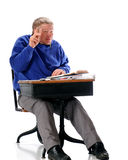 Not Too Sure. A mature student skeptically raising his hand as he sits in an old school desk covered in papers and books.  On a white background Royalty Free Stock Photos