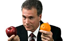 Not a True Comparison. Businessman impressing upon his group the fallacy of using unlike measures. Comparing apples and oranges Stock Photos