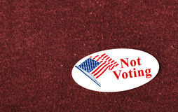"Not Voting. Closeup of a sticker with an American flag and the words ""Not Voting"" placed on a red shirt Royalty Free Stock Photography"