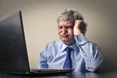 Not wanting to work. Senior man in front of computer with expression of listlessness Stock Photos