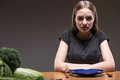 Not willing to concentrate on healthy nutrition. Revulsed woman sitting at the table with an empty plate in front of her Stock Photo