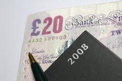 Nota £20 con il diario e la penna Fotografia Stock Libera da Diritti