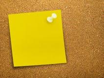 Nota amarilla brillante del recordatorio sobre tablón de anuncios Fotos de archivo libres de regalías